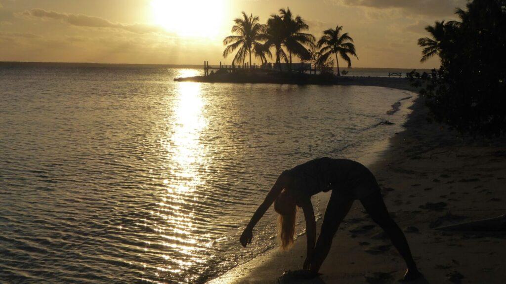 1 person laver vindmøller på strand ved solnedgang