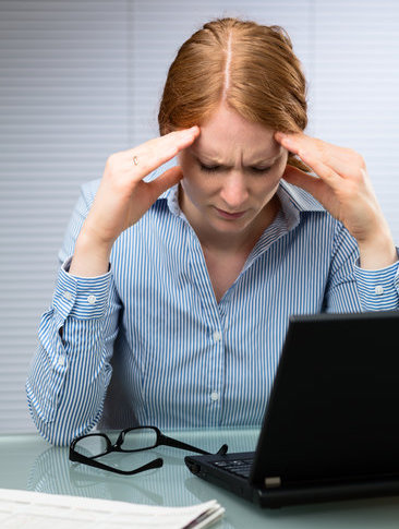 A stressed young business woman looks down and massages her head at her workplace.