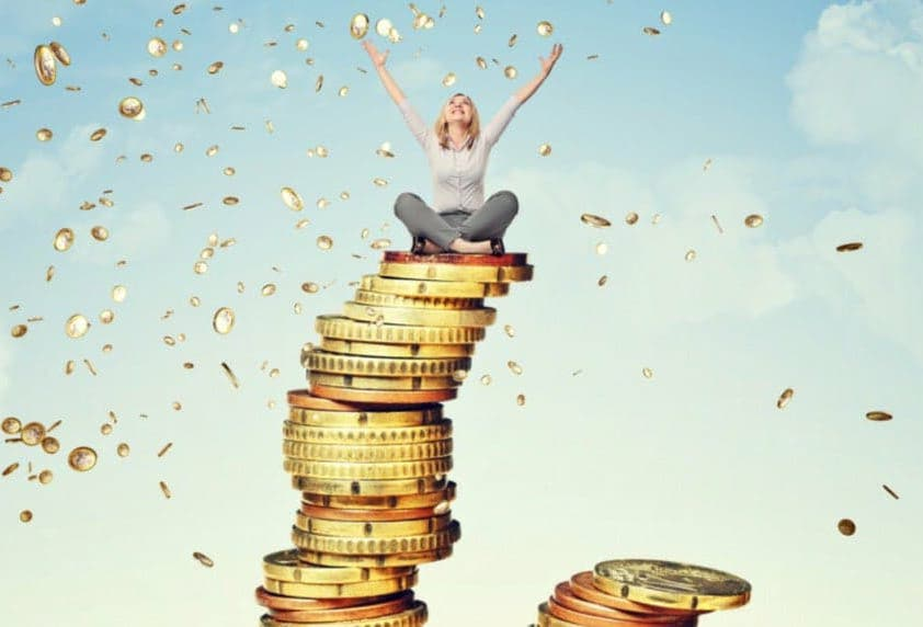 Kvinde sidder ovenpå en høj stak overdimisioneret mønter og jubler med armene over hovedet