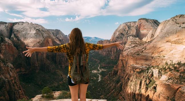 Kvinde står ved kæmpe bjergkæde og kigger ud over kløft med armene ud til siden med en følelse af frihed