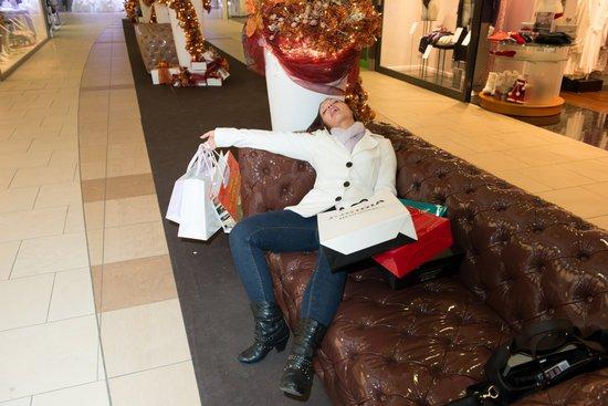Kvinde gået omkuld på sofa i indkøbscenter med masser af indkøbsposer i hænderne