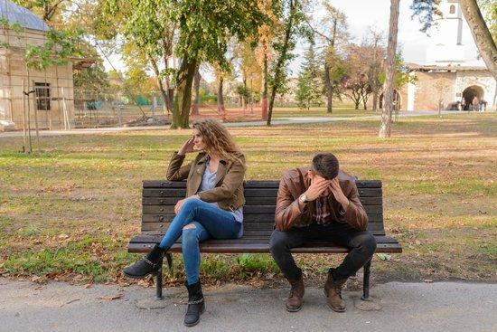 Mang og kvinde sidder på bænk med siden til hinanden efter en discussion