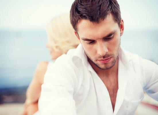 Mand og kvinde sidder ryg mod ryg på en strand