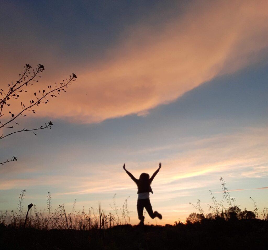 Person har begge arme i vejret i jubel over noget godt