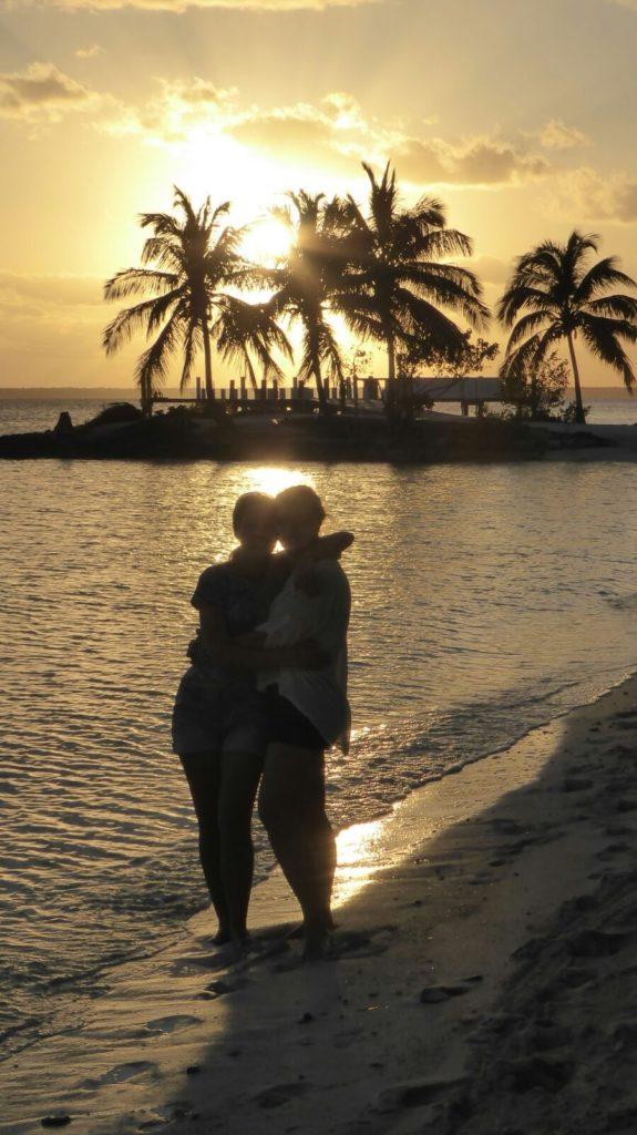 Solnedgang 2 personer strand palmer