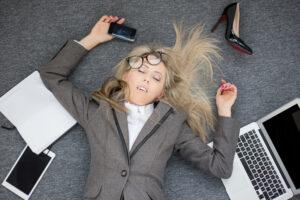 Kvinde ligger på gulvet gået omkuld i jakkesæt omgivet af papirer, computer og telefon