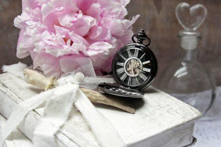 Lommeur på bord foran en lyserød blomst